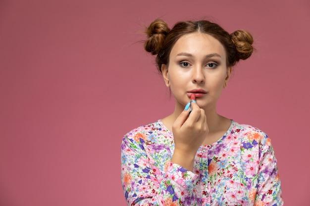 Mulher jovem de frente para a camisa com design floral e jeans azul pintando os lábios no fundo rosa