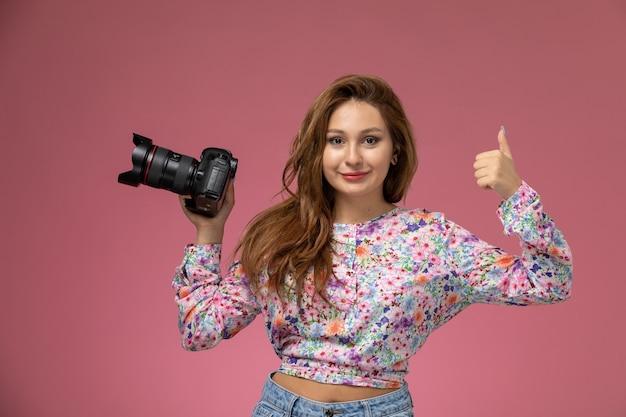Mulher jovem de frente para a camisa com design floral e jeans azul segurando uma câmera fotográfica preta no fundo rosa