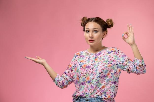 Mulher jovem de frente para a camisa com design floral e jeans azul, sorrindo e posando em um fundo rosa claro