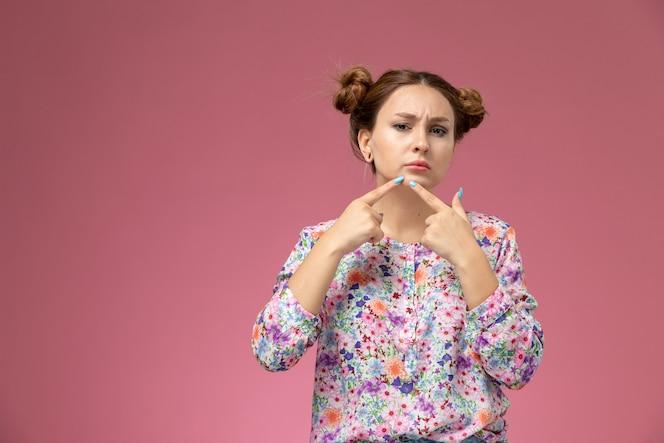 mulher jovem de frente para a camisa com design floral e jeans azul, tocando a acne no fundo rosa