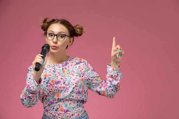 Mulher jovem de frente para a camisa com design floral e jeans cantando com o microfone sobre fundo claro