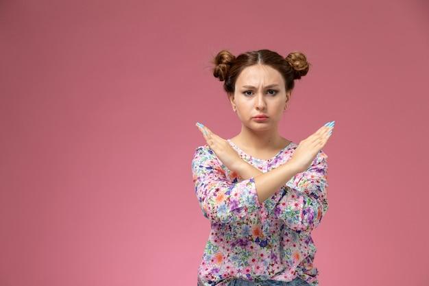 Mulher jovem de frente para a camisa com design florido e jeans azul. mostra o sinal de proibição no fundo rosa