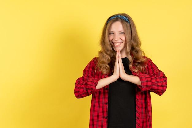 Mulher jovem de frente para a camisa quadriculada vermelha apenas de pé e sorrindo no modelo de fundo amarelo feminino cor de mulher humana