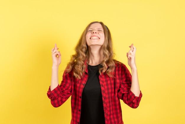 Mulher jovem de frente para a camisa quadriculada vermelha cruzando os dedos no fundo amarelo mulher emoção humana modelo moda garota