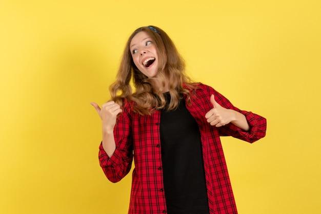 Mulher jovem de frente para a camisa quadriculada vermelha em pé e posando em emoções de cor de mulher humana de modelo de meninas de fundo amarelo