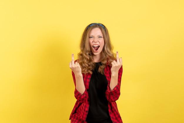 Mulher jovem de frente para a camisa quadriculada vermelha, posando e gritando em emoção de mulher modelo de cor humana de fundo amarelo