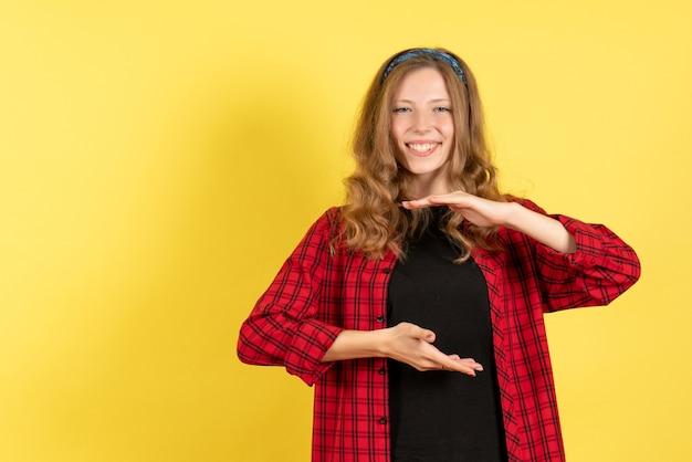 Mulher jovem de frente para a camisa quadriculada vermelha posando e sorrindo no fundo amarelo meninas mulher emoções modelo cor humana