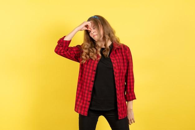 Mulher jovem de frente para a camisa quadriculada vermelha, sentindo-se estressada no fundo amarelo mulher emoção humana modelo moda garota