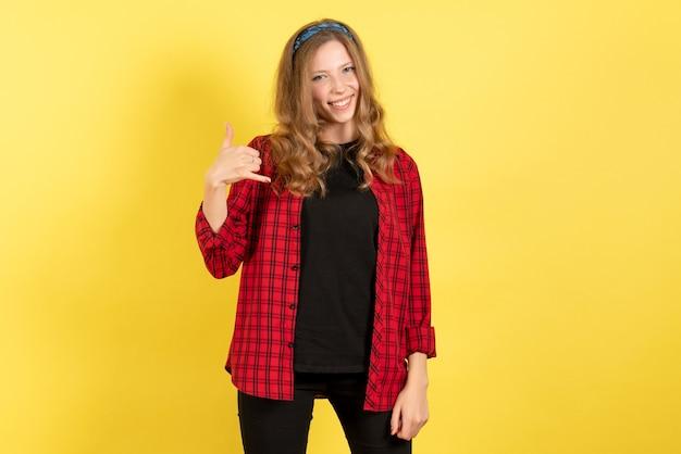 Mulher jovem de frente para a camisa quadriculada vermelha, sentindo-se feliz com o fundo amarelo mulher