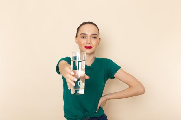 Mulher jovem de frente para a camisa verde escura e calça jeans azul segurando um copo de água na cor bege