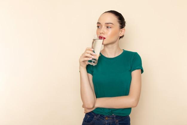Mulher jovem de frente para a camisa verde escura e jeans azul segurando um copo de água bebendo na cor bege