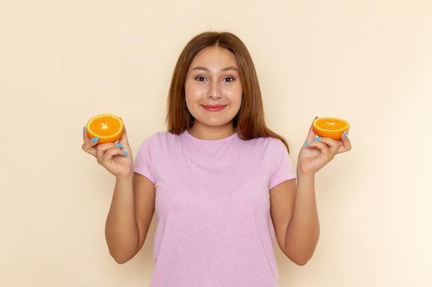 Mulher jovem de frente para a camiseta rosa e jeans azul segurando uma laranja com um sorriso