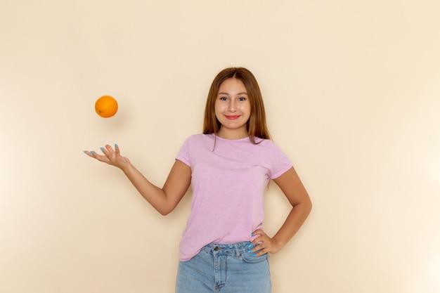 Mulher jovem de frente para a camiseta rosa e jeans azul segurando uma laranja focada nela e sorrindo