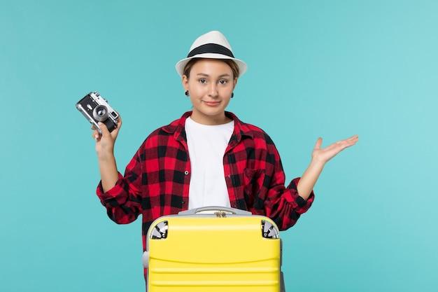 Mulher jovem de frente para a viagem e segurando a câmera na mesa azul