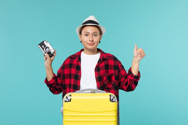 Mulher jovem de frente para a viagem e segurando a câmera no espaço azul