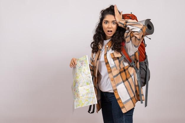 Mulher jovem de frente para caminhadas com mapa na natureza turística de fundo branco floresta campus montanha altura