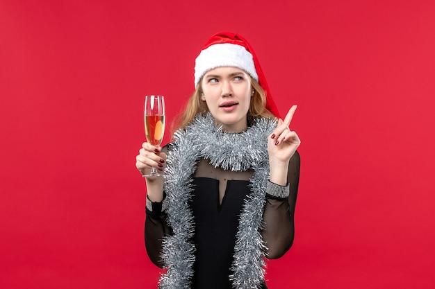 Mulher jovem de frente para celebrar o ano novo na parede vermelha férias natal emoção