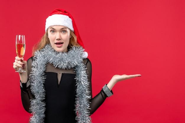 Mulher jovem de frente para comemorar o ano novo na parede vermelha férias emoção natal