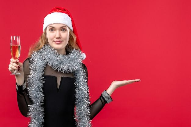 Mulher jovem de frente para comemorar o ano novo na parede vermelha.
