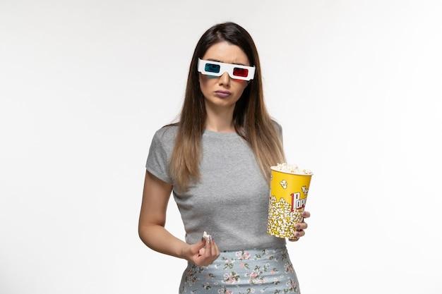 Mulher jovem de frente para comer pipoca e assistir filme com óculos de sol na mesa branca