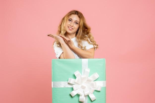 Mulher jovem de frente para dentro da caixa de presente azul