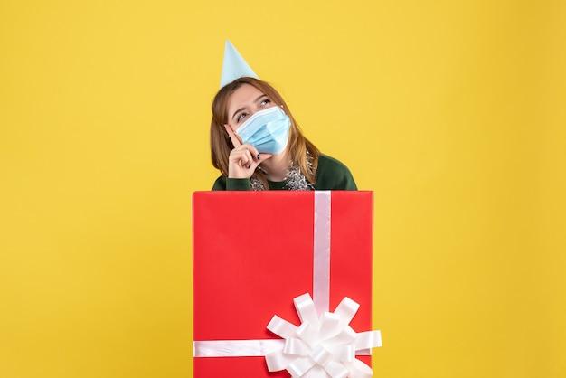 Mulher jovem de frente para dentro da caixa de presente com máscara estéril