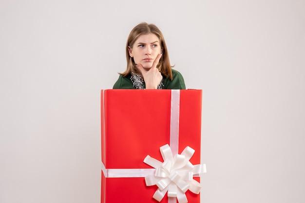 Mulher jovem de frente para dentro da caixa de presente pensando