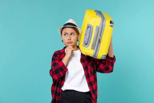 Mulher jovem de frente para ir de férias com seu grande saco pensando no espaço azul