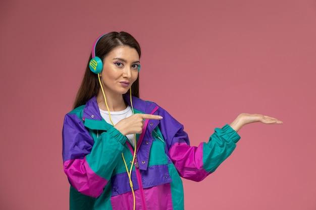 Mulher jovem de frente para o casaco moderno e colorido, fones de ouvido ouvindo música na parede rosa, foto colorida de roupas femininas