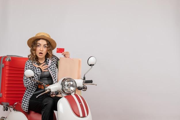 Mulher jovem de frente para o ciclomotor segurando o cartão e a sacola de compras colocando a mão no peito