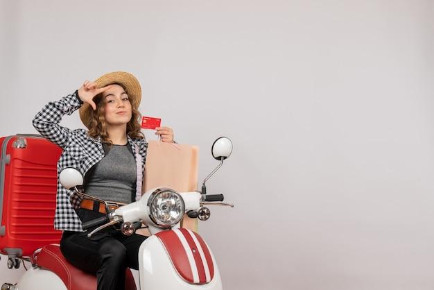 Mulher jovem de frente para o ciclomotor segurando o cartão e a sacola de compras