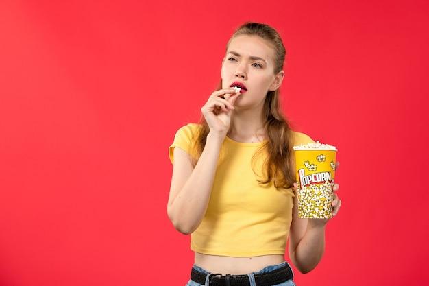 Mulher jovem de frente para o cinema segurando e comendo pacote de pipoca no filme de parede vermelha-clara.