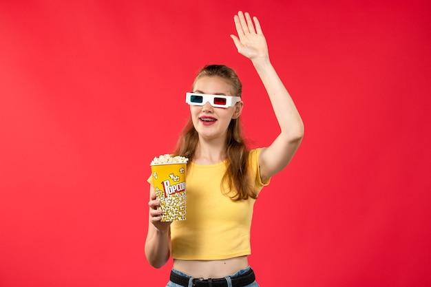 Mulher jovem de frente para o cinema segurando pacote de pipoca em óculos de sol -d na parede vermelha filmes teatro cinema divertido filme