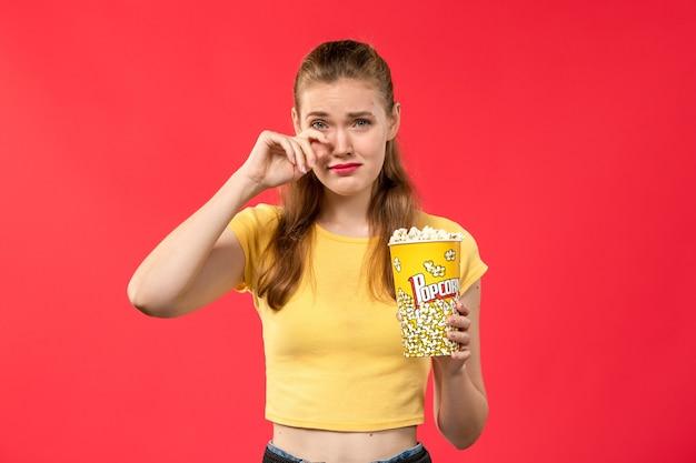 Mulher jovem de frente para o cinema segurando pipoca e choro falso na parede vermelha.