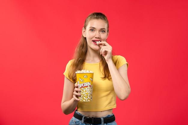 Mulher jovem de frente para o cinema segurando pipoca e comendo em filme de cinema de parede vermelha