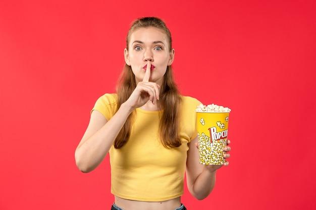Mulher jovem de frente para o cinema segurando pipoca e posando na parede vermelha.
