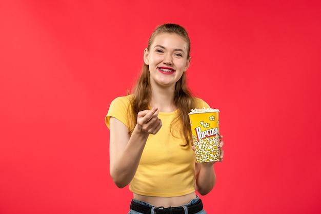 Mulher jovem de frente para o cinema segurando pipoca e rindo na parede vermelha.