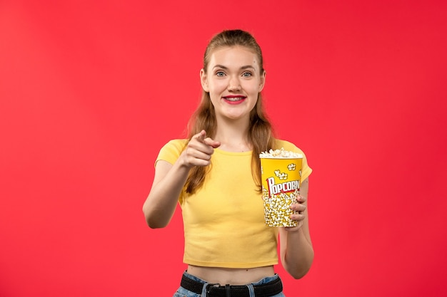 Mulher jovem de frente para o cinema segurando pipoca e sorrindo na parede vermelha.