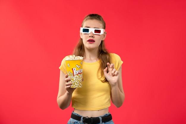 Mulher jovem de frente para o cinema segurando pipoca em óculos de sol na parede vermelha.