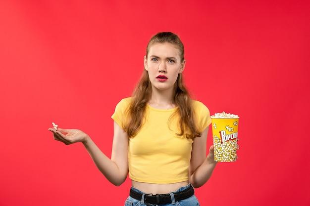 Mulher jovem de frente para o cinema segurando um pacote de pipoca e confusa na parede vermelha-clara.