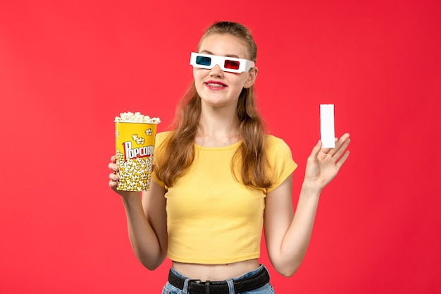 Mulher jovem de frente para o cinema segurando um pacote de pipoca e ingresso na parede vermelha.