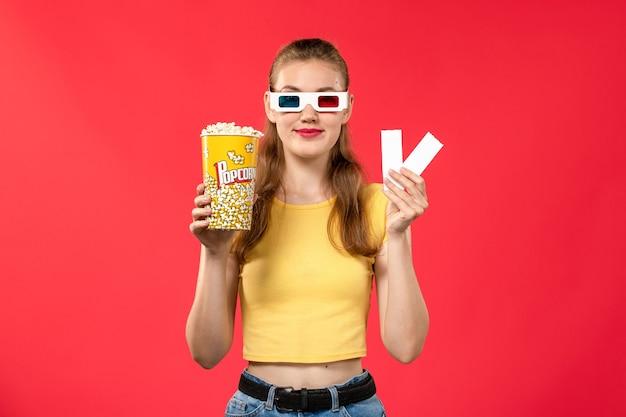 Mulher jovem de frente para o cinema segurando um pacote de pipoca e ingressos em um filme de cinema de cinema de parede vermelho-claro