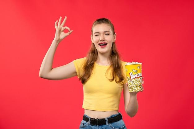 Mulher jovem de frente para o cinema segurando um pacote de pipoca e posando na parede vermelha-clara.