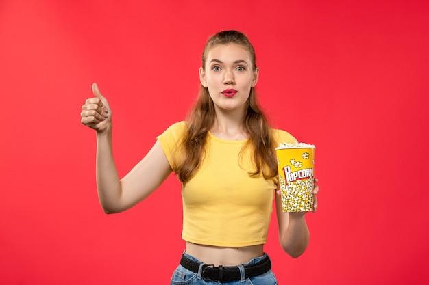 Mulher jovem de frente para o cinema segurando um pacote de pipoca e posando na parede vermelha.