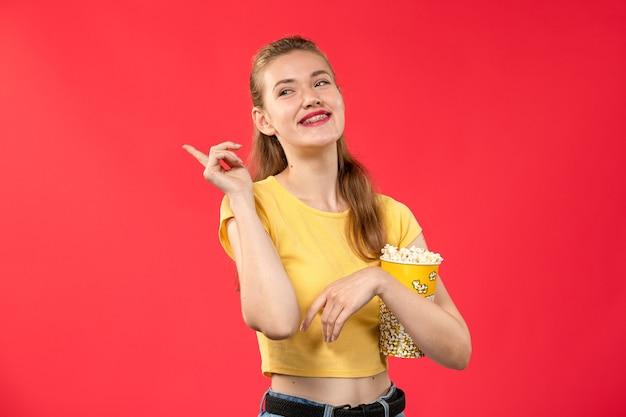 Mulher jovem de frente para o cinema segurando um pacote de pipoca e rindo de um filme de cinema de cinema de parede vermelho-claro