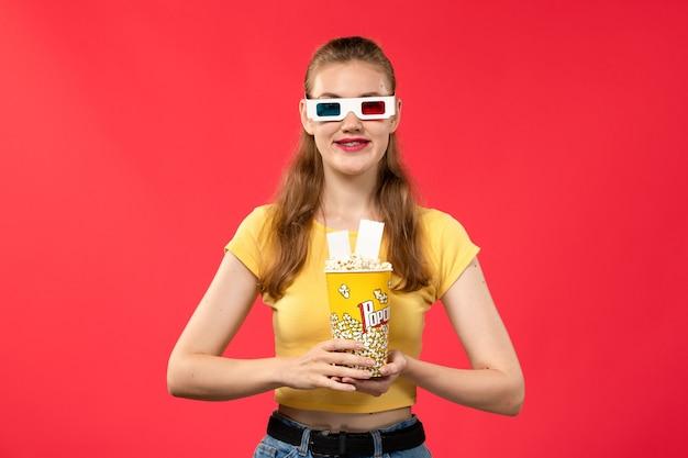 Mulher jovem de frente para o cinema segurando um pacote de pipoca em óculos de sol -d em filme de cinema de cinema de parede vermelho-claro