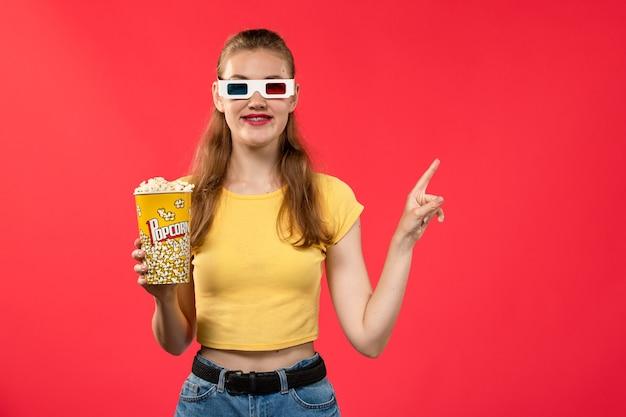 Mulher jovem de frente para o cinema segurando um pacote de pipoca em óculos de sol -d em filmes de parede vermelho-claro teatro cinema divertido filme