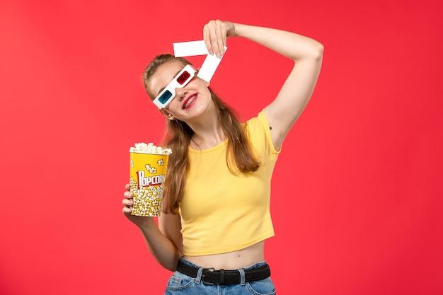 Mulher jovem de frente para o cinema segurando um pacote de pipoca em óculos de sol segurando os ingressos na parede vermelha cinemas cinema filme garota