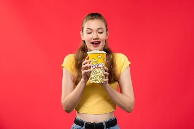 Mulher jovem de frente para o cinema segurando um pacote de pipoca no filme de cinema de parede vermelha clara.