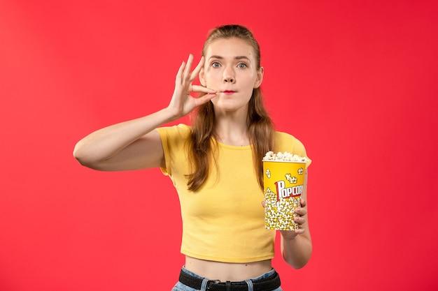 Mulher jovem de frente para o cinema segurando um pacote de pipoca no filme de cinema de parede vermelho-claro.
